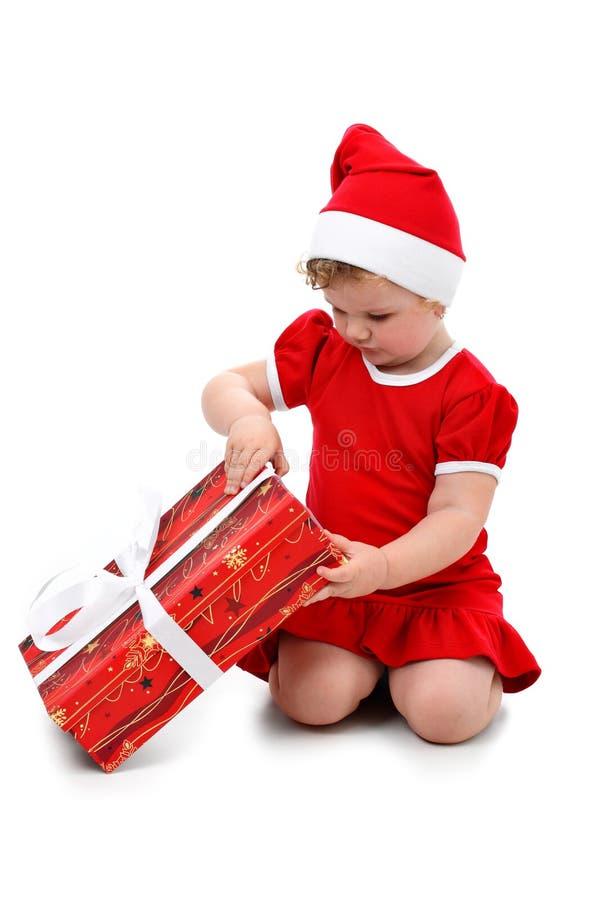 Baby girl in Santa hat unpacking Christmas present royalty free stock photos