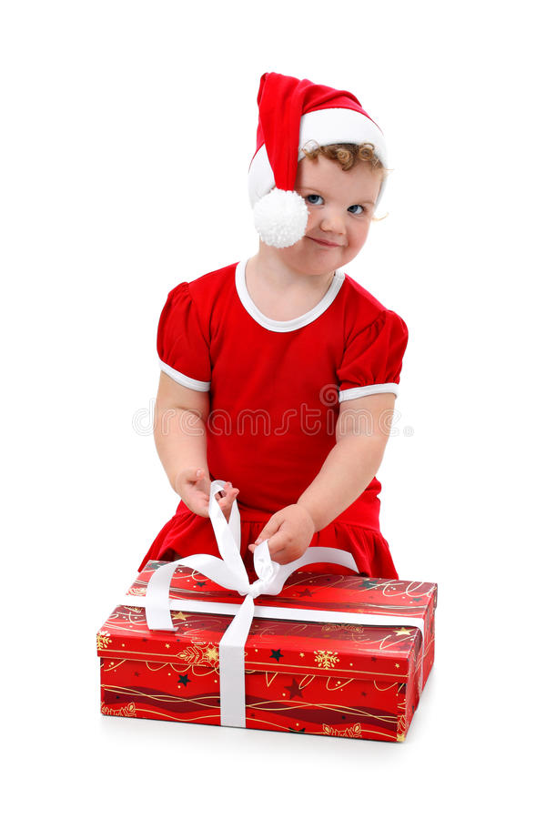 Baby girl in Santa hat unpacking Christmas present royalty free stock photography