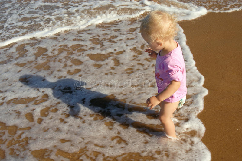 Baby girl at the seashore: first experience. stock images
