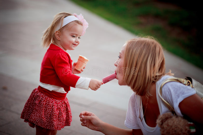 Baby girl sharing ice-cream with mother. A photo of baby girl sharing ice-cream with mother royalty free stock image