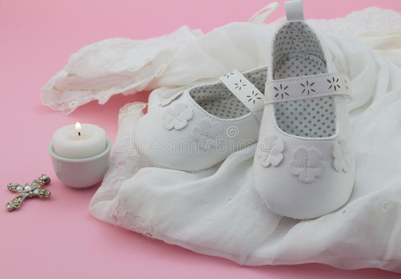 Baby girl shoes, cross and candle on white lace with pink background stock photo