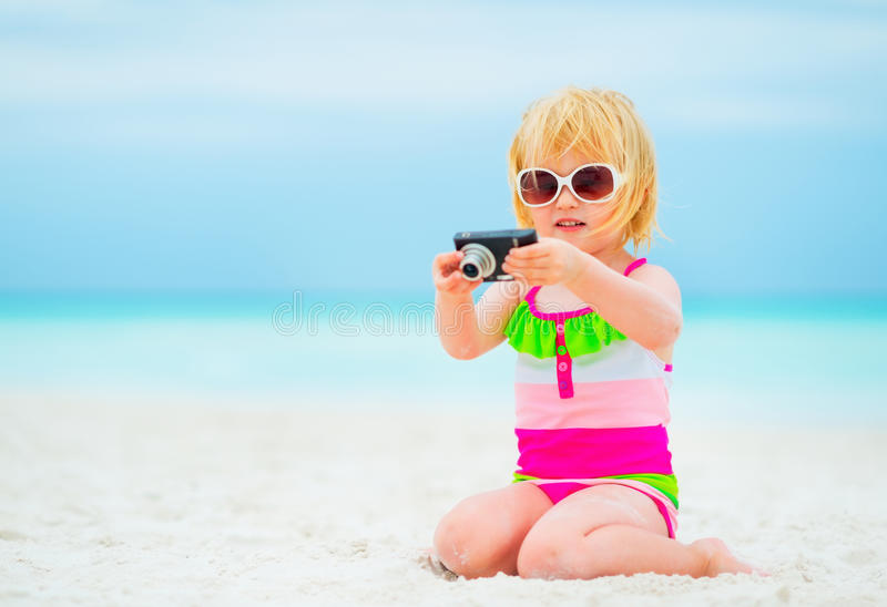 Baby girl sitting on beach and using photo camera. Baby girl in sunglasses sitting on beach and using photo camera royalty free stock photos