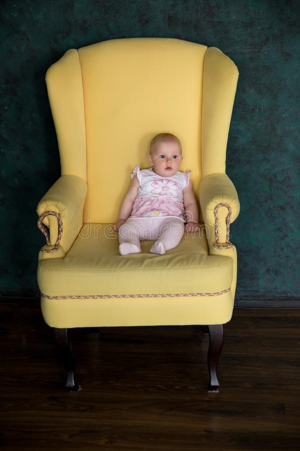 Baby Girl Sitting on Big Armchair in Studio stock images