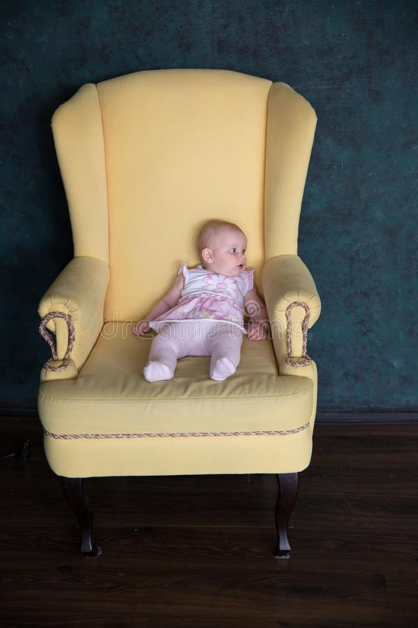 Baby Girl Sitting on Big Armchair in Studio. Baby Girl Sitting on Big Armchair. Yellow Armchair. Serious Infant Looking to Distance. Child Wearing Pink Dress stock photography