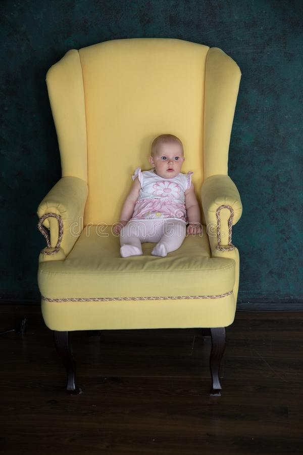 Baby Girl Sitting on Big Armchair in Studio. Baby Girl Sitting on Big Armchair. Yellow Armchair. Serious Infant Looking to Distance. Child Wearing Pink Dress stock photo