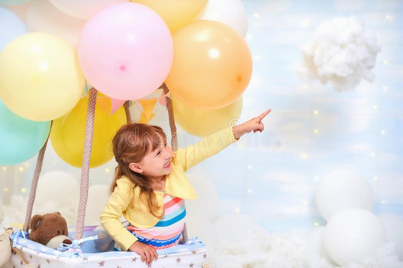 Baby girl sitting on a cloud next to a basket of balloon in the clouds, traveling and flying with Aviator hat and glasses. Baby girl sitting in a basket of royalty free stock image