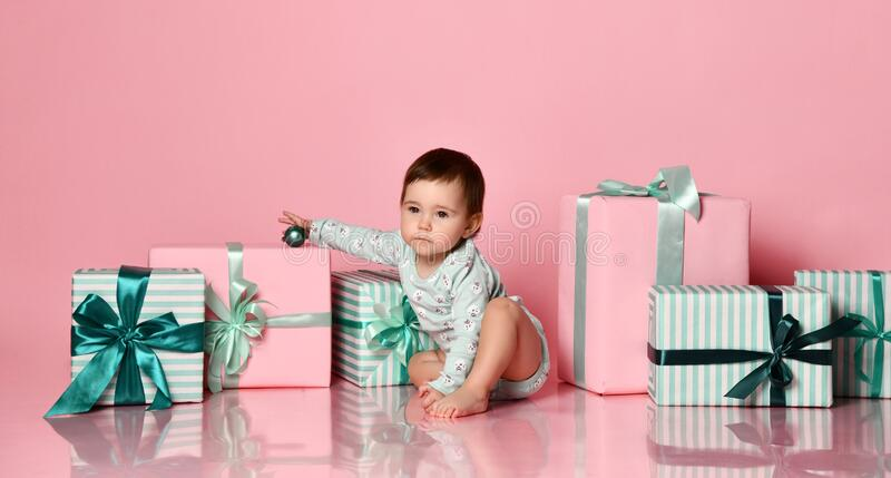 Baby girl sitting on the floor with gift box stock photos
