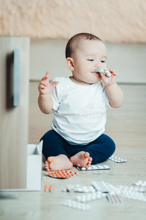 Baby, girl sitting on the floor in the hands of pills. Pulled out of the box or out of the closet stock photos