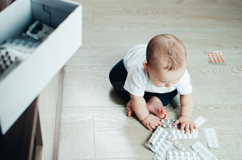 Baby, girl sitting on the floor in the hands of pills. Pulled out of the box or out of the closet royalty free stock photos