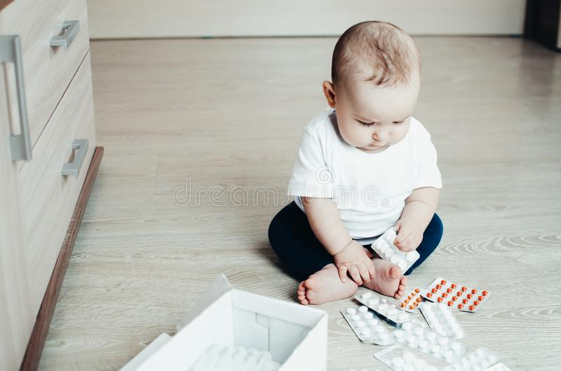Baby, girl sitting on the floor in the hands of pills. Pulled out of the box or out of the closet royalty free stock images
