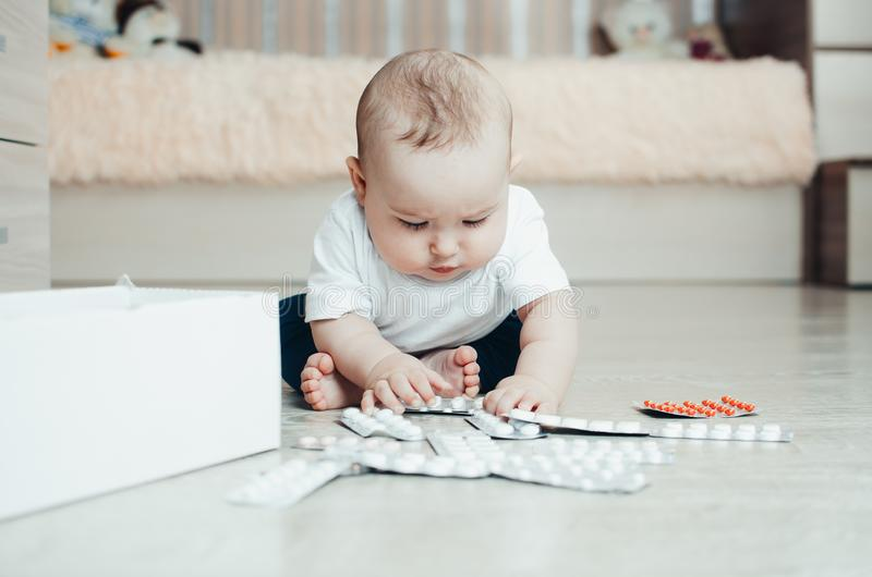 Baby, girl sitting on the floor in the hands of pills. Pulled out of the box or out of the closet stock photography