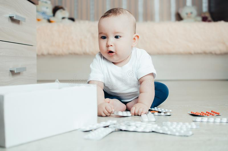 Baby, girl sitting on the floor in the hands of pills. Pulled out of the box or out of the closet royalty free stock image