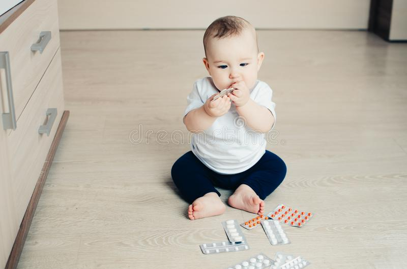 Baby, girl sitting on the floor in the hands of pills. Pulled out of the box or out of the closet royalty free stock photography