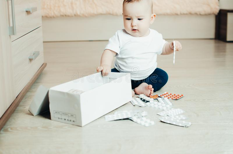 Baby, girl sitting on the floor in the hands of pills. Pulled out of the box or out of the closet stock image