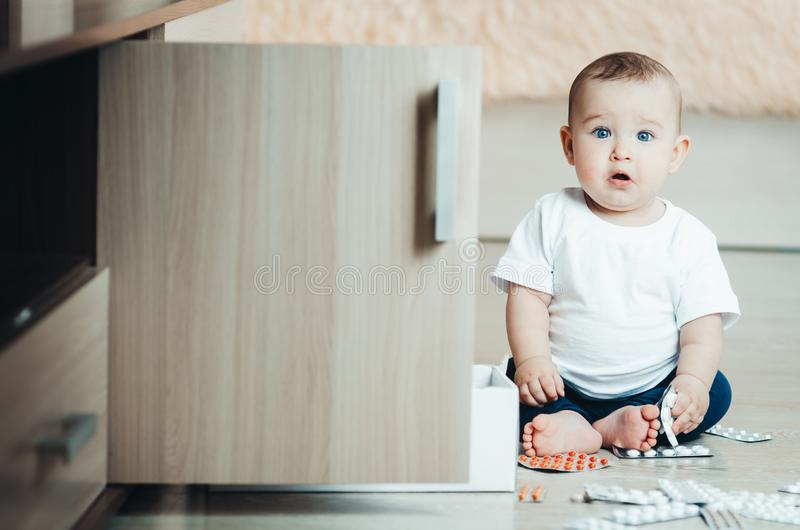 Baby, girl sitting on the floor in the hands of pills. Pulled out of the box or out of the closet stock images