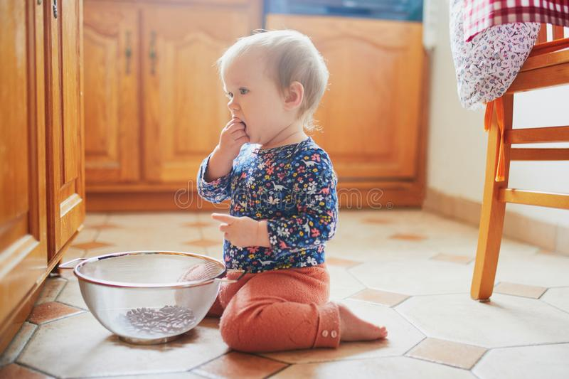 Baby girl sitting on the floor in the kitchen and playing with kitchenware. Little child at home royalty free stock photography