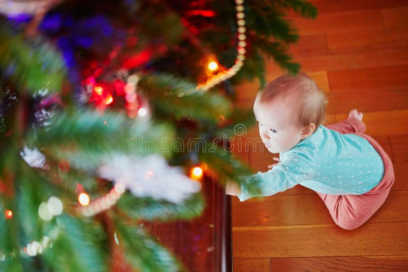 Baby girl sitting on the floor under Christmas tree stock photography