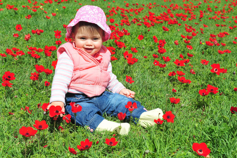 Baby Girl Sitting in Flowery Field. An image of a baby girl sitting in a green field with red poppies stock image