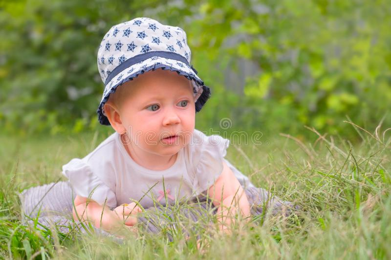 Happy childhood concept. Baby girl in hat, panama. Toddler lying in the grass. stock images