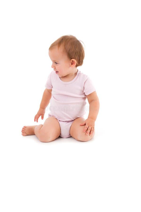 Baby girl sitting between heels. Wearing short sleeve bodysuit stock photography