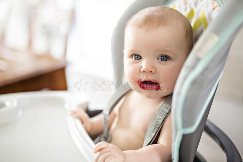 Baby girl sitting in high chair for eating stock photos