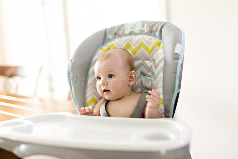 Baby girl sitting in high chair ready for eating royalty free stock photography
