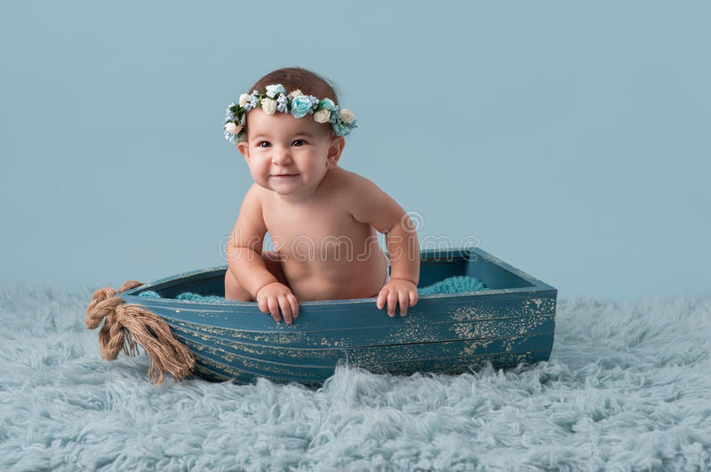 Baby Girl Sitting in a Little Boat. A studio shot of a smiling nine month old baby girl wearing a floral crown and sitting in a little boat stock images