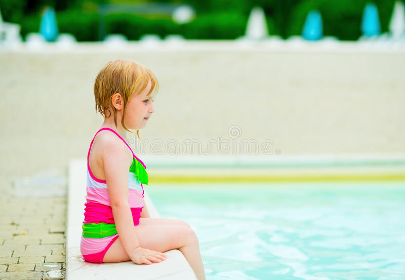 Baby girl sitting near swimming pool. Baby girl in bikini sitting near swimming pool royalty free stock photography