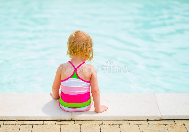 Baby girl sitting near swimming pool. rear view. Baby girl sitting in swimsuit near swimming pool. rear view stock photos