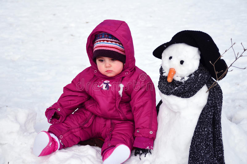 Baby girl sitting outdoor next to snowman. Baby girl dressed with warmer sitting next to snowman royalty free stock image