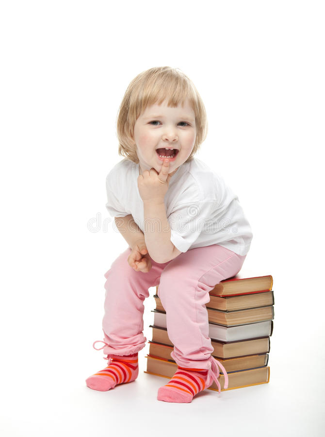 The baby girl is sitting on the pile of books. And proping up chin stock photos