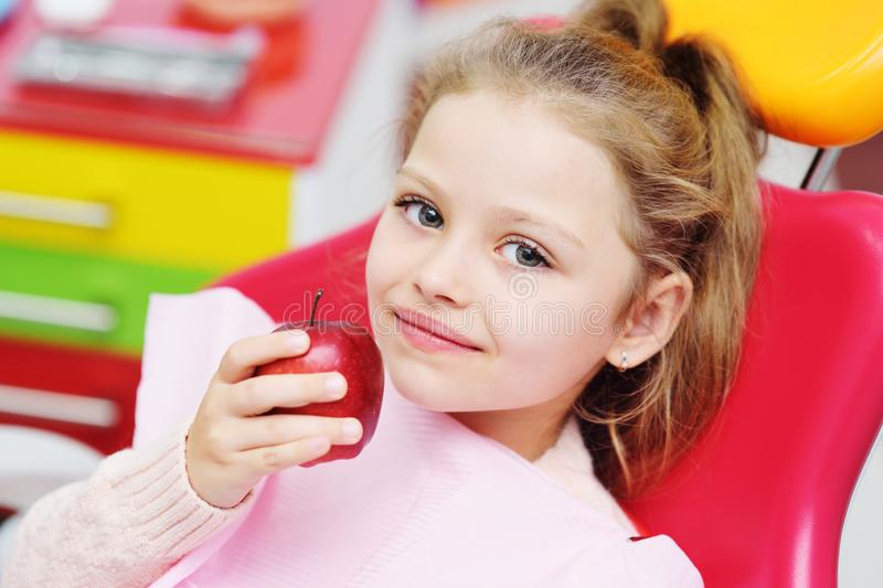 Baby girl sitting in a red dental chair smiling with a red Apple in her hands. royalty free stock images