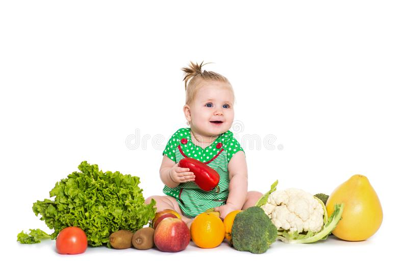 Baby girl sitting surrounded by fruits and vegetables, isolated on white stock image