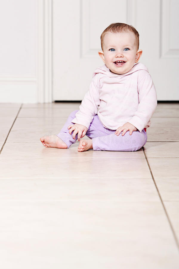 Baby Girl Sitting on Tiled Floor royalty free stock image
