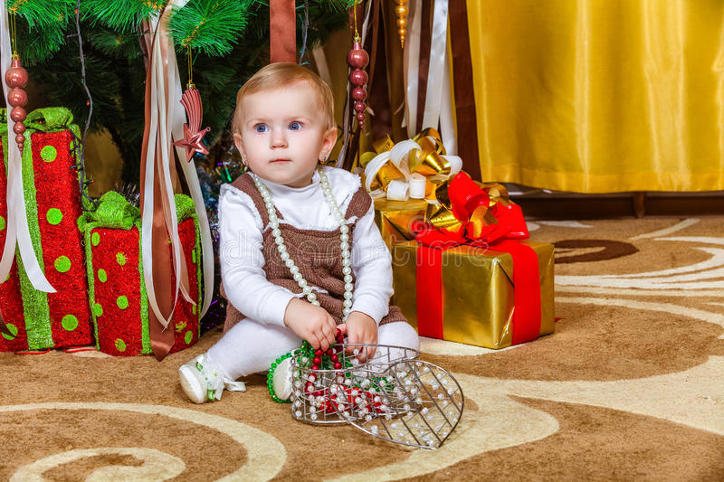 Download Baby Girl Sitting Under Christmas Tree In Room Royalty Free Stock Photos - Image: 37527178