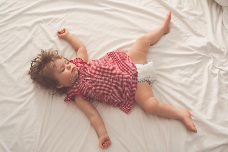 Baby girl sleeping on back with open arms and without pacifier in a bed with white sheets. Peaceful sleeping in a bright. Room. Pastel retro toned. Soft focus stock photos