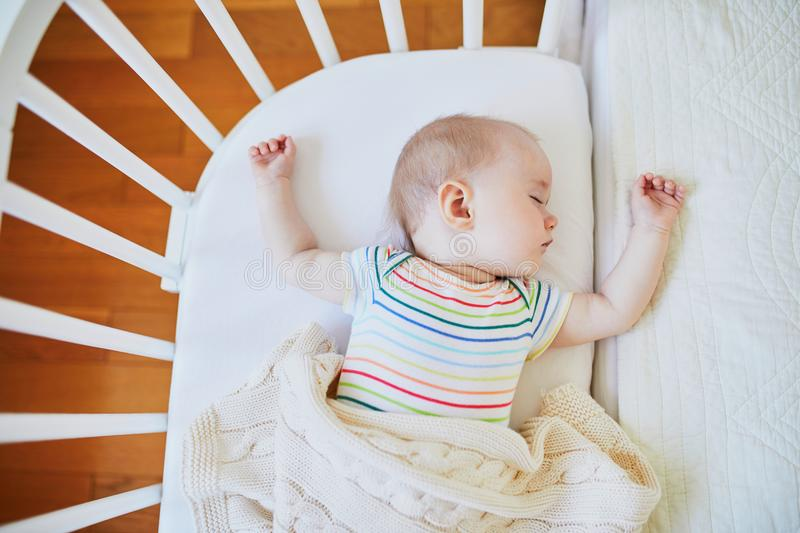 Baby girl sleeping in co-sleeper crib. Adorable baby girl sleeping in co-sleeper crib attached to parents` bed. Little child having a day nap in cot. Infant kid stock photos
