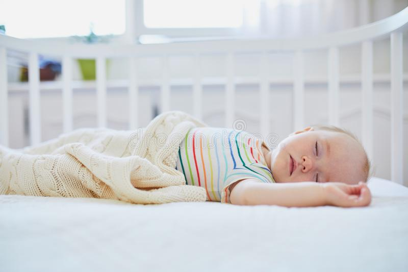 Baby girl sleeping in co-sleeper crib. Adorable baby girl sleeping in co-sleeper crib attached to parents` bed. Little child having a day nap in cot. Infant kid royalty free stock photography
