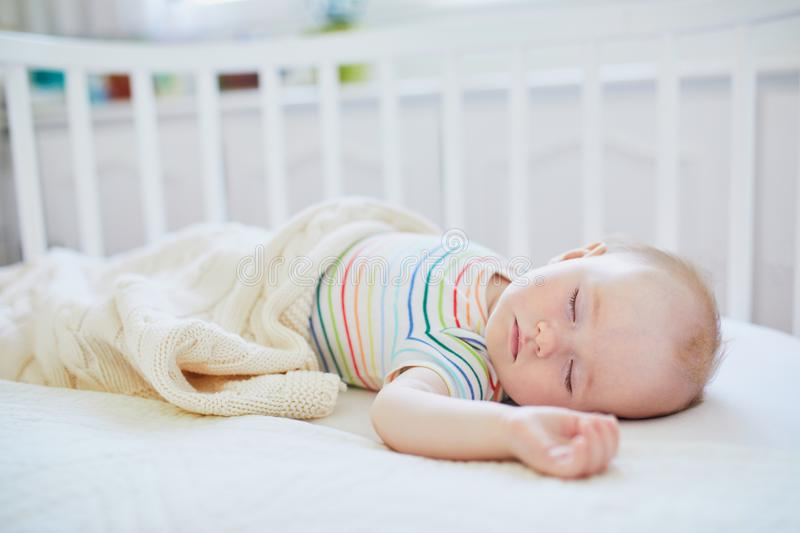 Baby girl sleeping in co-sleeper crib. Adorable baby girl sleeping in co-sleeper crib attached to parents` bed. Little child having a day nap in cot. Infant kid stock photo