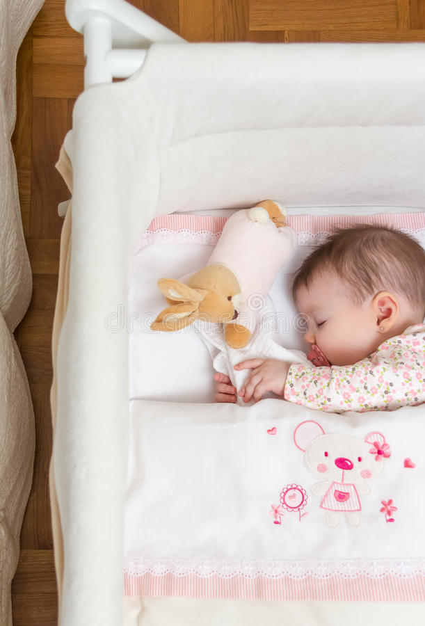 Baby girl sleeping in a cot with pacifier and toy. Portrait of cute baby girl sleeping in a cot with pacifier and stuffed toy royalty free stock image