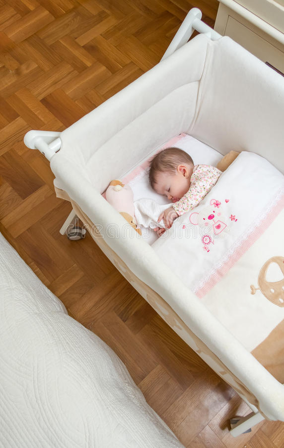 Baby girl sleeping in a cot with pacifier and toy. Portrait of cute baby girl sleeping in a cot with pacifier and stuffed toy royalty free stock photography