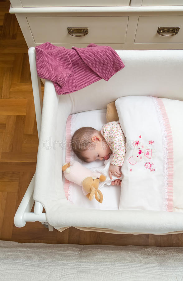 Baby girl sleeping in a cot with pacifier and toy. Portrait of cute baby girl sleeping in a cot with pacifier and stuffed toy stock photos