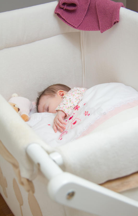 Baby girl sleeping in a cot with pacifier and toy. Portrait of cute baby girl sleeping in a cot with pacifier and stuffed toy royalty free stock photo