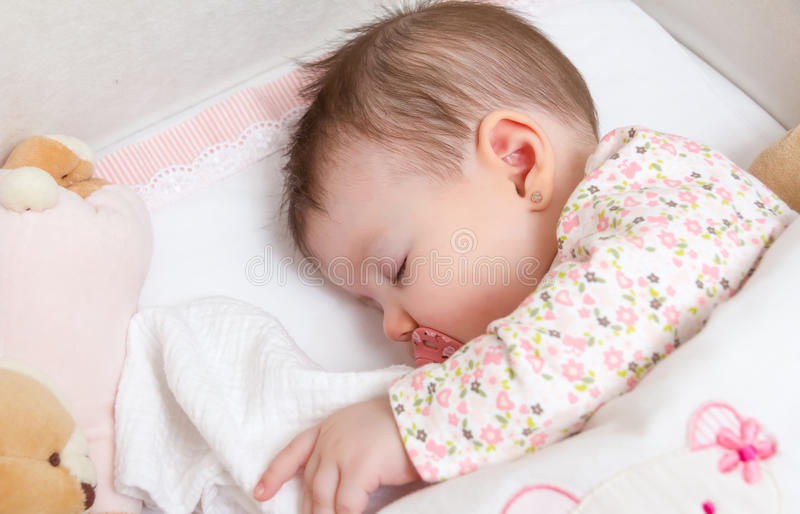 Baby girl sleeping in a cot with pacifier and toy stock photography