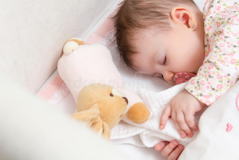 Baby girl sleeping in a cot with pacifier and toy royalty free stock photo
