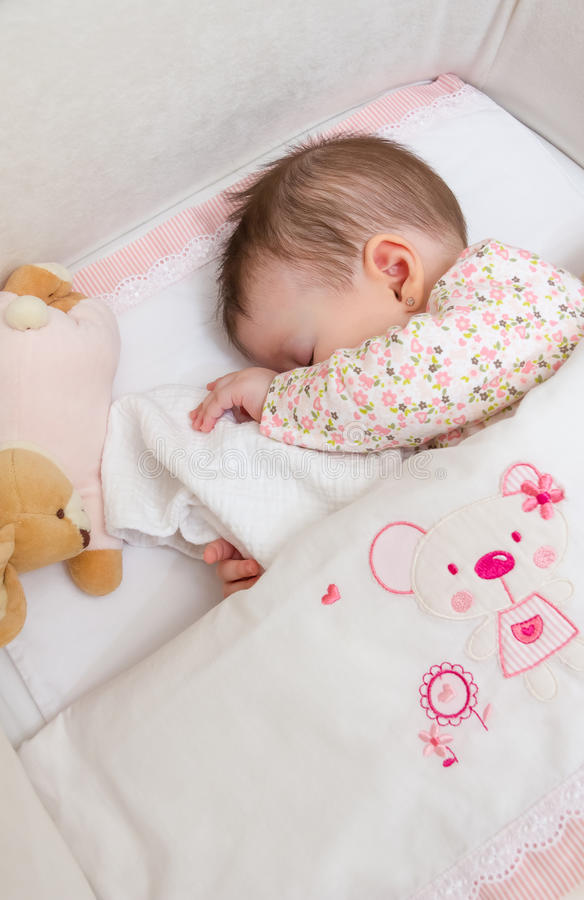 Baby girl sleeping in a cot with pacifier and toy. Portrait of cute baby girl sleeping in a cot with pacifier and stuffed toy stock images