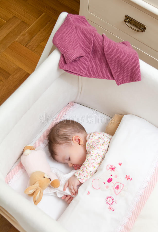 Baby girl sleeping in a cot with pacifier and toy. Portrait of cute baby girl sleeping in a cot with pacifier and stuffed toy royalty free stock photos