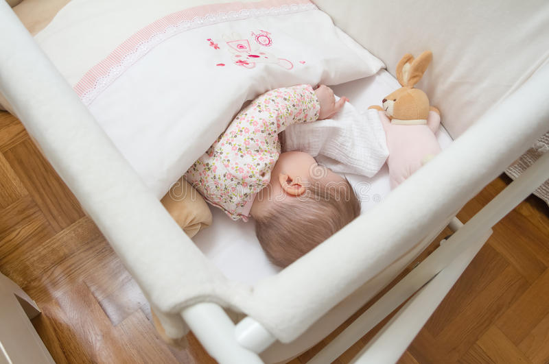 Baby girl sleeping in a cot with pacifier and toy. Portrait of cute baby girl sleeping in a cot with pacifier and stuffed toy stock photo