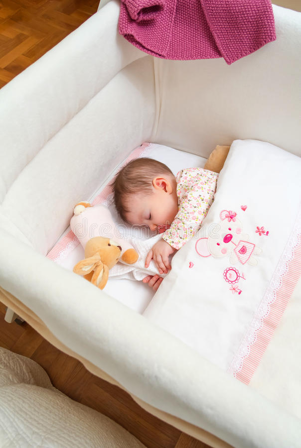 Baby girl sleeping in a cot with pacifier and toy stock image