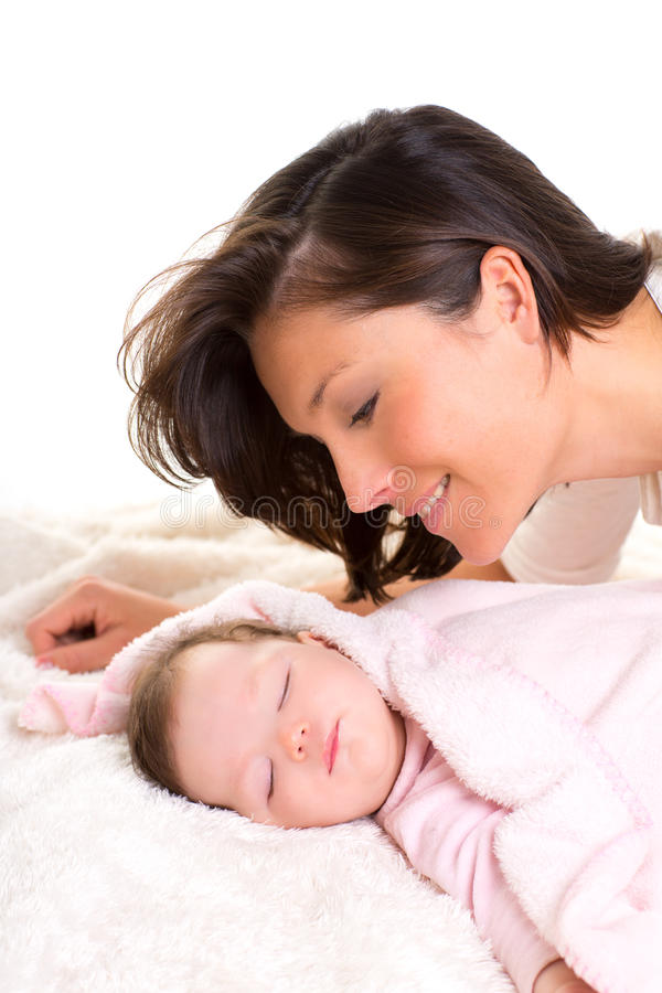 Baby girl sleeping with mother care near. On white fur royalty free stock photo